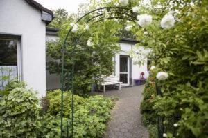 Rosenbogen vor dem Haus mit Blick auf die Eingangstür